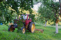Tractor with harrow the garden apple trees in yard old red Royalty Free Stock Photography