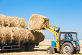 Tractor loading hay bales on truck trailer Royalty Free Stock Photo