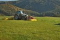 Tractor mowing mountain meadow in czech republic Royalty Free Stock Photo