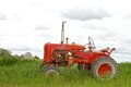 Tractor parked in grassy field scene depicting an old red a on a cloudy day with barn the distance Royalty Free Stock Photo