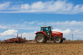 Tractor and plow farmer plowing the field cultivating in the field red farm with a in a farm field Royalty Free Stock Images