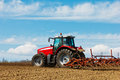 Tractor and plow farmer plowing the field cultivating in the field red farm with a in a farm field Royalty Free Stock Image