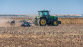 Tractor plowing on dry field Royalty Free Stock Photo