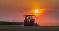Tractor plowing field at dusk Royalty Free Stock Photography