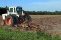 Tractor plowing the field a kansas farmer his with a small white Stock Photography