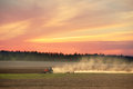 Tractor plowing the the land at sunset Royalty Free Stock Photography