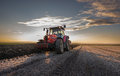 Tractor plowing red at sunset Royalty Free Stock Image