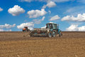 Tractor sowing field seeder Stock Photos