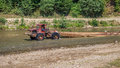 Tractor transporting cut wood along river Valea Vaserului Royalty Free Stock Photo