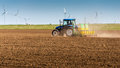 Tractor working on field with windmill turbines farmer farm spring time horizon Stock Images