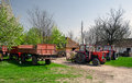 Tractors and trailers on the old fashioned farm sunny spring day Stock Images