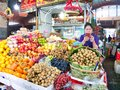 A trader checks her mobiole phone with fruit and vegetables for sale at a market stall in Phnom Penh, Cambodia Royalty Free Stock Photo