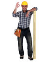 Tradesman leaning on planks of wood and giving the a ok sign Stock Photo