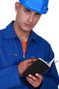 Tradesman writing in his agenda small Stock Photos