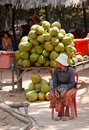 Tradeswoman of coconuts at angkor cambodia feb an unidentified sits by her table with about thousands tourists visit khmer Stock Photo