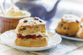 Traditional afternoon tea with scones jam and cream blue teapot crockery light summery teashop menu Stock Image