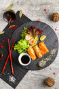 Traditional Asian food, fried rolls with salad and vegetables on the black plate Royalty Free Stock Photo