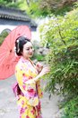 Traditional Asian Japanese woman bride hold a red umbrella smiling in a garden Royalty Free Stock Photo