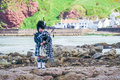 Traditional bagpiper in the scottish highlands Royalty Free Stock Photo