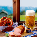 Traditional bavarian cuisine for oktoberfest with regional pork and beef loaf served with salted pretzels a spicy dip and large Royalty Free Stock Photo