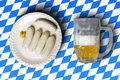 Traditional bavarian sausages on white plate and beer in front o