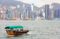 Traditional Boat in front of Hong Kong Harbour Skyline Royalty Free Stock Photo