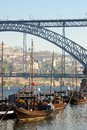 Traditional boats with wine barrels porto portugal in the river douro and bridge Stock Photo