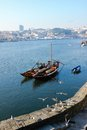 Traditional boats with wine barrels porto portugal in the river douro and view of vila nova do gaia Stock Photography