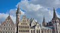 Traditional buildings in gent and towers the blue but clouded sky of Royalty Free Stock Photo