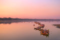 Traditional burmese boats on Taungthaman Lake at sunset, in Amarapura, Mandalay Myanmar Royalty Free Stock Photo