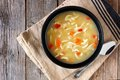 Traditional chicken noodle soup, above scene on rustic wood Royalty Free Stock Photo
