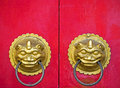 Traditional chinese doors with brass handles symbolic of lion s heads it s believe to ward off evil and usher in good luck for the Royalty Free Stock Photo