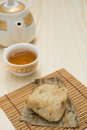 Traditional Chinese glutinous rice dumpling with cup of tea and teapot vertical Royalty Free Stock Photo