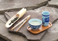 Traditional chinese tea ceremony accessories tea cups and bambo bamboo scoop of green on the stone table selective focus on Stock Image