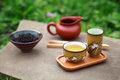 Traditional chinese tea ceremony accessories tea cups and pitch pitcher on the stone table selective focus on cup Stock Image