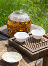 Traditional chinese tea ceremony accessories tea leaves in boil boiling water a glass pot and cups selective focus Royalty Free Stock Image
