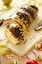 stock image of  Traditional Christmas biscuit roll with chocolate cream,chocolate chips and gold stars on the holiday table close-up.