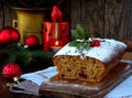 Traditional Christmas fruit cake decorated with powdered sugar and mas decorations, candle. copy space. style rustic. selective fo Royalty Free Stock Photo