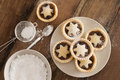 Traditional christmas fruit mince pies decorated with pastry stars on a kitchen table ready to be sprinkled with powdered icing Royalty Free Stock Photo