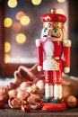 Traditional christmas wooden nutcracker colorful red in the figure of a king with assorted whole nuts in their shells in front of Stock Image