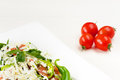 Traditional classic Shopska salad with tomatoes, peppers, cucumbers and cheese in white dish on white wooden table. Bulgarian cuis Royalty Free Stock Photo