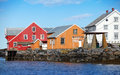 Traditional coastal norwegian village with colorful wooden houses on rocky coast Stock Images