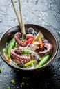 Traditional dish with octopus and noodles on black rock Royalty Free Stock Photos