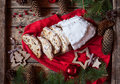 Traditional Dresdner German Christmas cake Stollen with raising, berries and nuts. Holiday xmas decorations. Royalty Free Stock Photo