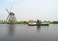 Traditional Dutch Windmill and Boat on the canal at Kinderdijk Royalty Free Stock Photo
