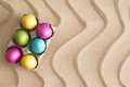 Traditional easter egg hunt at the beach with a box of colorful painted eggs hidden on golden sand with a decorative wavy pattern Royalty Free Stock Photography