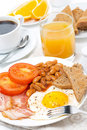 Traditional english breakfast with eggs bacon beans coffee fried and juice vertical close up Stock Photos