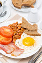 Traditional english breakfast with fried eggs bacon and beans vertical top view Royalty Free Stock Images