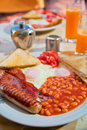 Traditional english breakfast fried sausages eggs bacon tomato baked beans toasts and orange juice Stock Photography