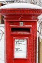 Traditional english red post box a photographed after a winter snow storm Stock Image